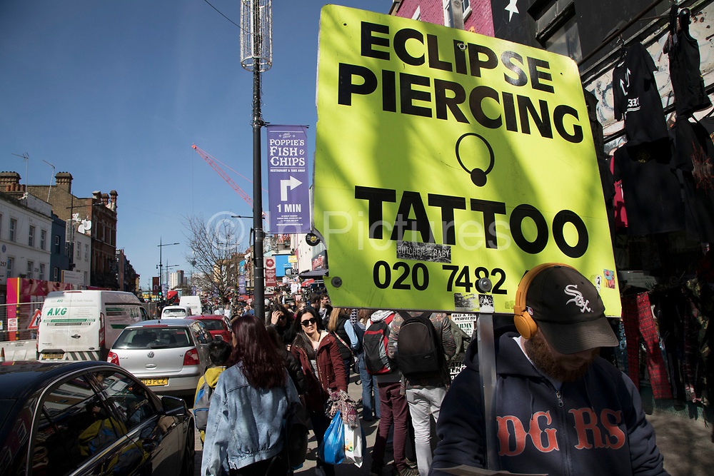 Tattoo and piercing sign at the busy hang out for young Londoners and tourists in Camden Town, London, England, United Kingdom. Camden Town is famed for its market, warren of fashion and shops near Regent's Canal, and is a haven of alternative counter culture.