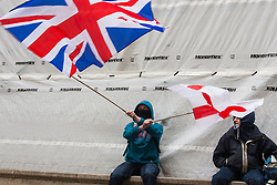 Whitehall, London, April 4th 2015. As PEGIDA UK holds a poorly attended rally on Whitehall, scores of police are called in to contain counter protesters from various London anti-fascist movements. PICTURED: A PEGIDA supporter waves a Union Jack and an England flag as he waits for their rally to begin.