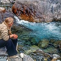 A trekker sits beside a stream in the Khumbu region of Nepal's Himalaya.
