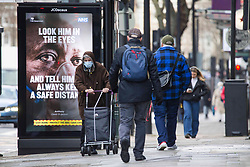 © Licensed to London News Pictures.28/01/2021, London,UK. Members of the public walk past a covid-19 sign in Euston, central London during the third national lockdown. Photo credit: Marcin Nowak/LNP