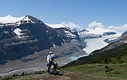 A hiker sees Saskatchewan Glacier from Parker Ridge, in Banff National Park, Alberta, Canada. This is part of the big Canadian Rocky Mountain Parks World Heritage Site declared by UNESCO in 1984.