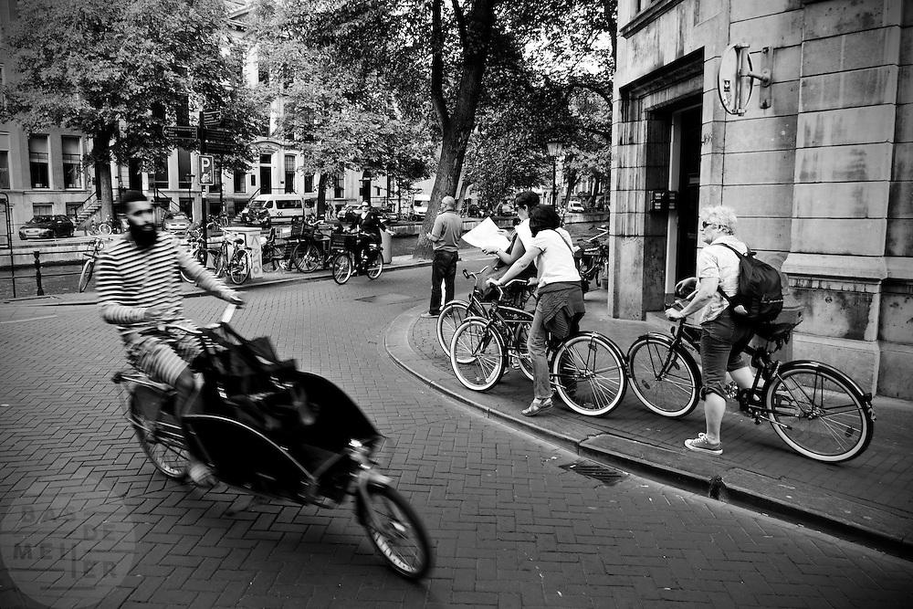 In Amsterdam fietst een man met een bakfiets voorbij een groep toeristen met een huurfiets die op een kaart kijken waar ze heen moeten gaan. <br /> <br /> In Amsterdam, a man riding a cargo bike passes a group of tourists on a rented bicycle on a map to see where they need to go.