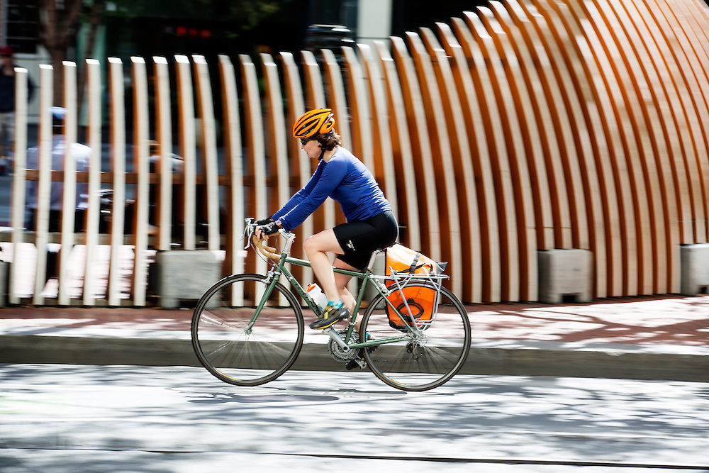 Een vrouw fietst met de helm op over Market Street in San Francisco. De Amerikaanse stad San Francisco aan de westkust is een van de grootste steden in Amerika en kenmerkt zich door de steile heuvels in de stad. Ondanks de heuvels wordt er steeds meer gefietst in de stad.<br /> <br /> Cyclists in San Francisco. The US city of San Francisco on the west coast is one of the largest cities in America and is characterized by the steep hills in the city. Despite the hills more and more people cycle.