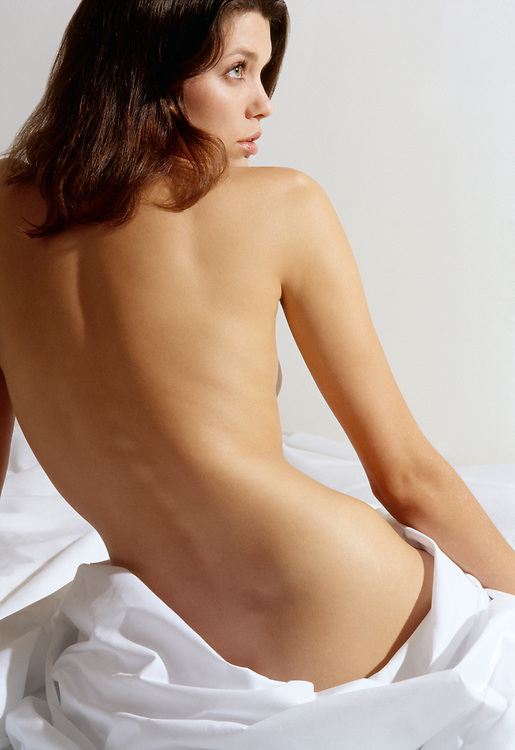 Rear view of nude woman in bed with face in profile. White background