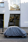 A small car is protected by plastic covering while parked on St John Street in Clerkenwell on 26th February 2021, in London, England.