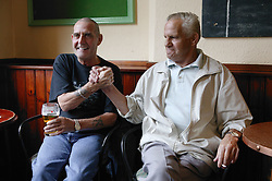 Two men hand wrestling in a pub,