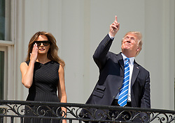 United States President Donald J. Trump, right, points skywards as he prepares look at the partial eclipse of the sun from the Blue Room Balcony of the White House in Washington, DC, USA, on Monday, August 21, 2017. Photo by Ron Sachs/CNP/ABACAPRESS.COM
