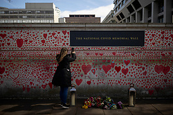 © Licensed to London News Pictures. 08/04/2021. London, UK. A woman takes a photograph of a name she added to the National Covid Memorial Wall, which has now been completed with approximately 150,000 hearts painted on the Thames Embankment opposite the Houses of Parliament to remember those who lost their lives to Covid-19. Members of the public are invited to walk the length of the memorial, and campaigners are asking Prime Minister Boris Johnson to make the memorial permanent. Photo credit: Rob Pinney/LNP