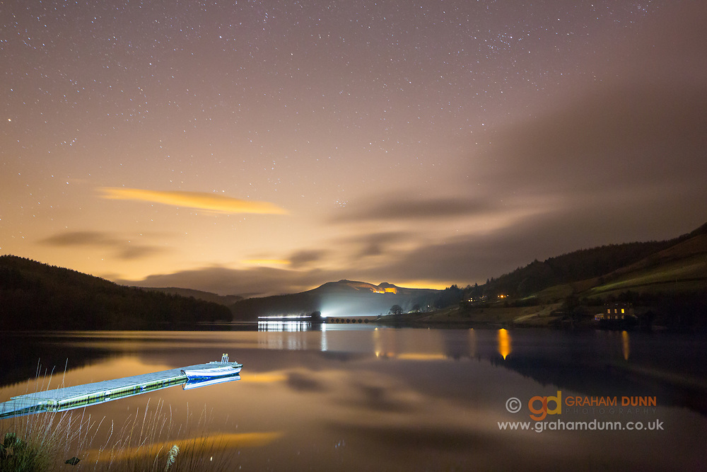 A calm Ladybower Reservoir reflects the night sky and its amazing display of stars. Crook Hill can be seen in the distance. Derbyshire, Peak District National Park, England, UK. February, winter, 2014.