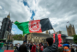 © Licensed to London News Pictures. 18/08/2021. LONDON, UK.  A member of the British Afghan community waves a national flag during a protest in Parliament Square in reaction to the Taliban takeover of Afghanistan.  Parliament has been recalled early for Boris Johnson, Prime Minister, and MPs to debate the UK government's decision to bring 20,000 vulnerable Afghan refugees, particularly women and children, to the country..  Photo credit: Stephen Chung/LNP