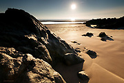 An outcrop of headland just onto the North end of the vast sandy Aberffraw beach. The sunset reflects off large tidal pools left on the main beach. The mountains of the Llyn Peninsula can just be made out on the horizon.
