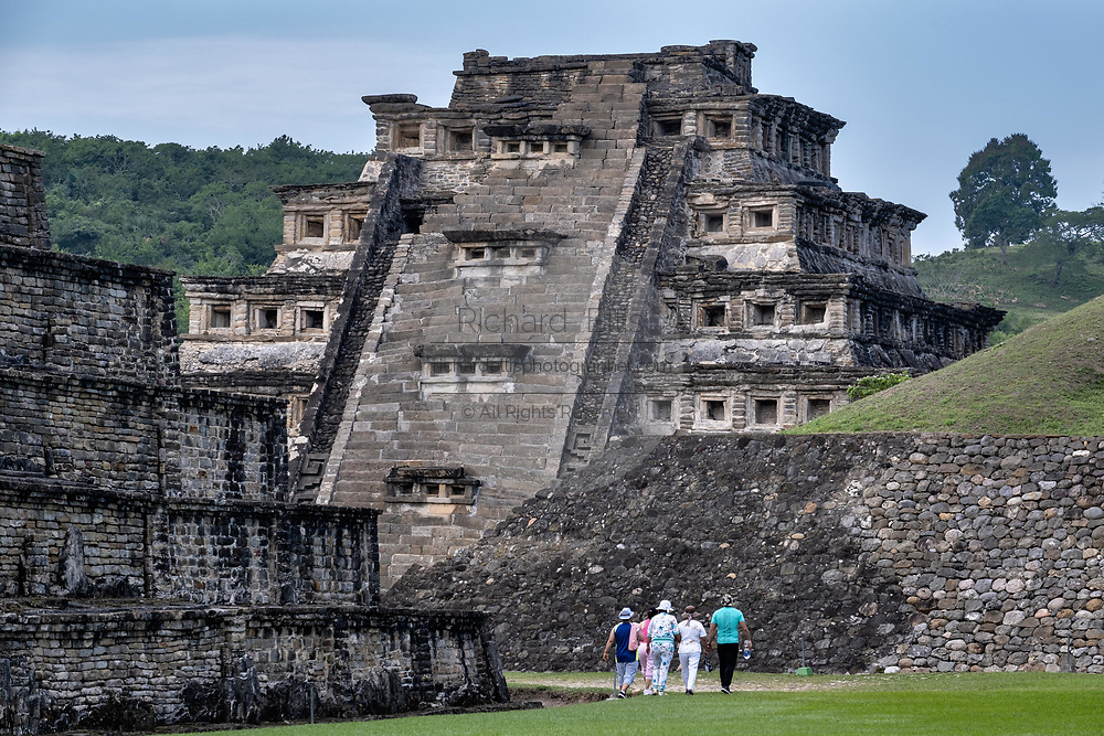 Tourists walk toward the Mesoamerica Pyramid of the Niches at the pre-Columbian archeological complex of El Tajin in Tajin, Veracruz, Mexico. El Tajín flourished from 600 to 1200 CE and during this time numerous temples, palaces, ballcourts, and pyramids were built by the Totonac people and is one of the largest and most important cities of the Classic era of Mesoamerica.