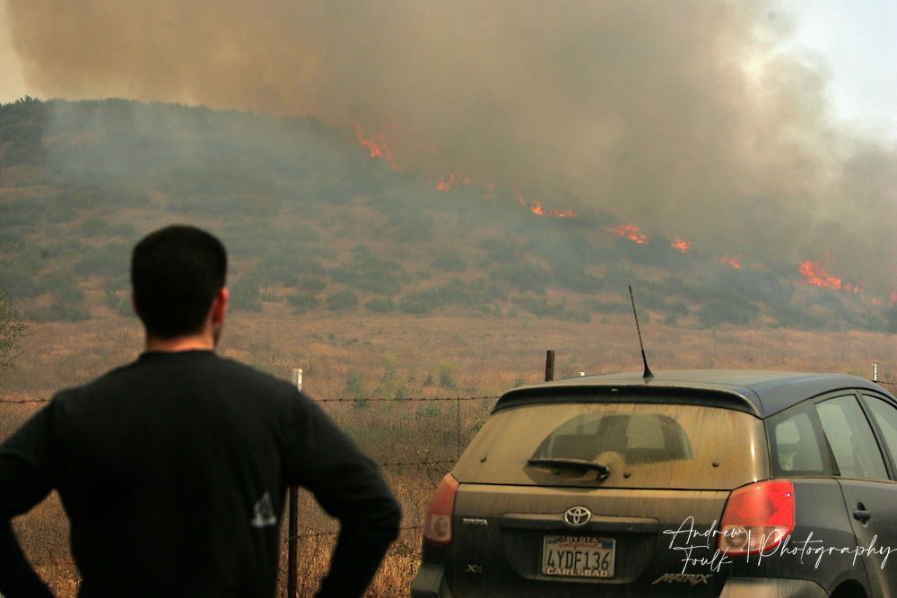 /Andrew Foulk/ For the Californian/.A  French Valley resident watches as flames crest the ridge of a hill just South of Scott Road. The fire started at around 2pm in the area just North of Keller Road and South of Scott Road. The Fire consumed an estimated 200 acres and caused the closure of Scott, and Winchester Roads.