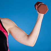 A woman curling a barbell. Photographed with studio lighting in front of a blue backdrop.
