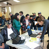 Paralegal Devon Kovac, right, with the law firm of Egolf, Ferlic, Martinez and Harwood LLC helps individuals with paperwork Thursday morning at the Shiprock Chapter house during a meeting concerning the 2015 Gold King Mine spill.