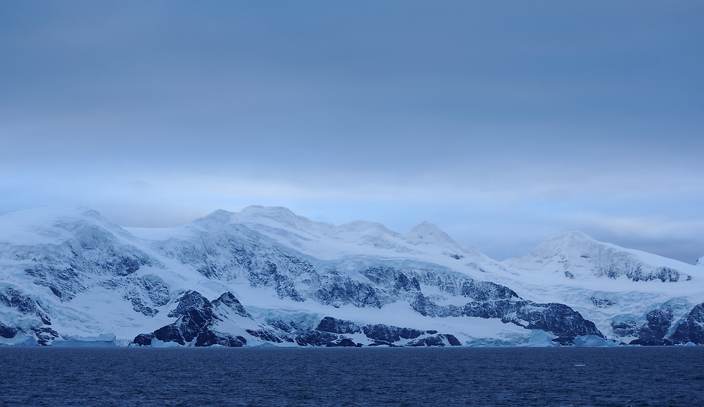 A stormy sky above the snow covered mountains and glaciers of Coronation Island.  Coronation Island, South Orkney Islands, Antarctica. 28Feb16