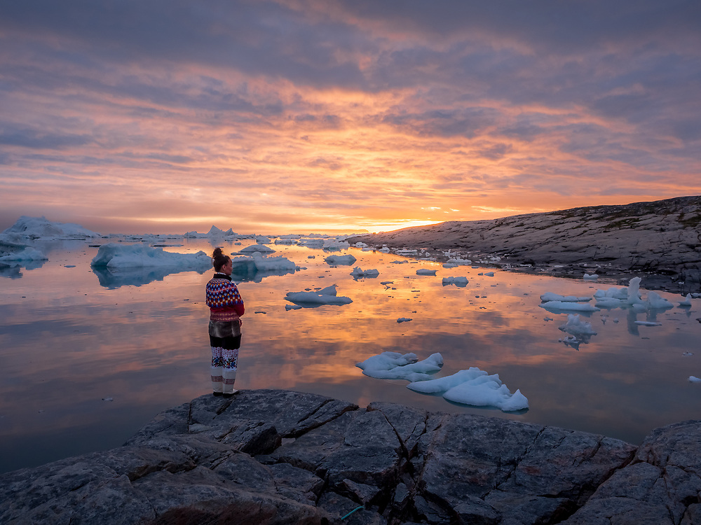 Woman in traditional Greenlandic costume overlooking the bay at Oqaatsut.