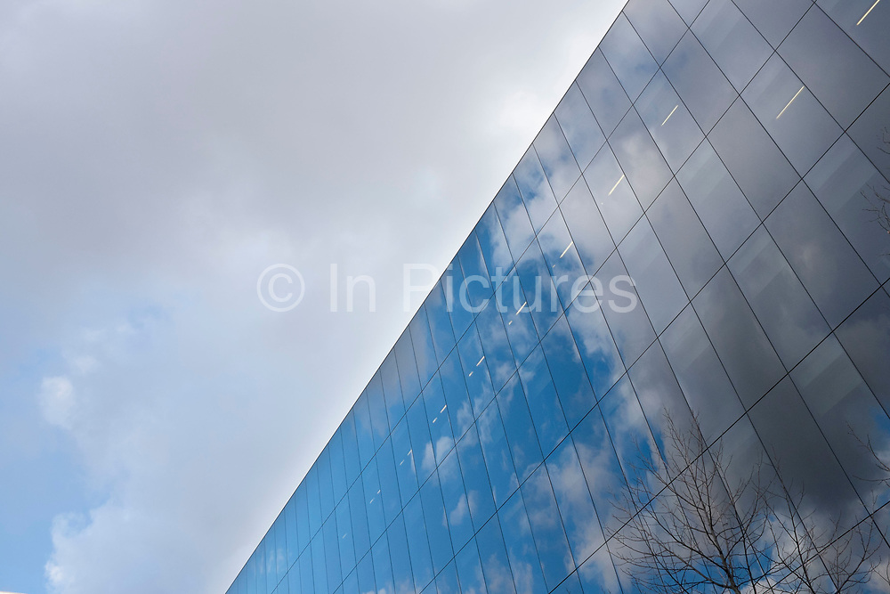 Glass building reflecting the clouds in a blue sky. Modern architecture interacting with nature at More London, UK. More London is an office development containing many professional services and financial services firms.