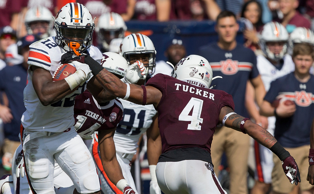 Auburn wide receiver Eli Stove (12) avoids Texas A&M defensive back Derrick Tucker (4) for more yards after a catch during the third quarter of an NCAA college football game on Saturday, Nov. 4, 2017, in College Station, Texas. (AP Photo/Sam Craft)