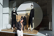 A tired young woman yawns beneath retail mannequins on Regent Street in Westminster, on 26th February, in London, England.