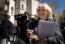 © Licensed to London News Pictures. 23/04/2021. London, UK. Former Post Office sub-postmaster Jo Hamilton holds a glass of Prosecco as she reacts to the verdict outside The High Court. The Appeal Court has cleared the names of a group of 42 sub-postmasters - some of whom were jailed for stealing money after the Horizon accounting software was installed at Post Offices. At a previous High Court hearing a judge found the Fujitsu accounting system had major faults and defects. The Post Office has already agreed to pay £58m in a settlement with more than 500 sub-postmasters. <br /> Six convictions were overturned last year . Photo credit: Peter Macdiarmid/LNP