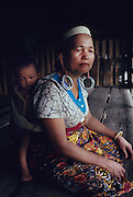 DAYAK, MALAYSIA. Sarawak, Borneo, South East Asia. Woman with baby in papoose in longhouse. Tropical rainforest and one of the world's richest, oldest eco-systems, flora and fauna, under threat from development, logging and deforestation. Home to indigenous Dayak native tribal peoples, farming by slash and burn cultivation, fishing and hunting wild boar. Home to the Penan, traditional nomadic hunter-gatherers, of whom only one thousand survive, eating roots, and hunting wild animals with blowpipes. Animists, Christians, they still practice traditional medicine from herbs and plants. Native people have mounted protests and blockades against logging concessions, many have been arrested and imprisoned.