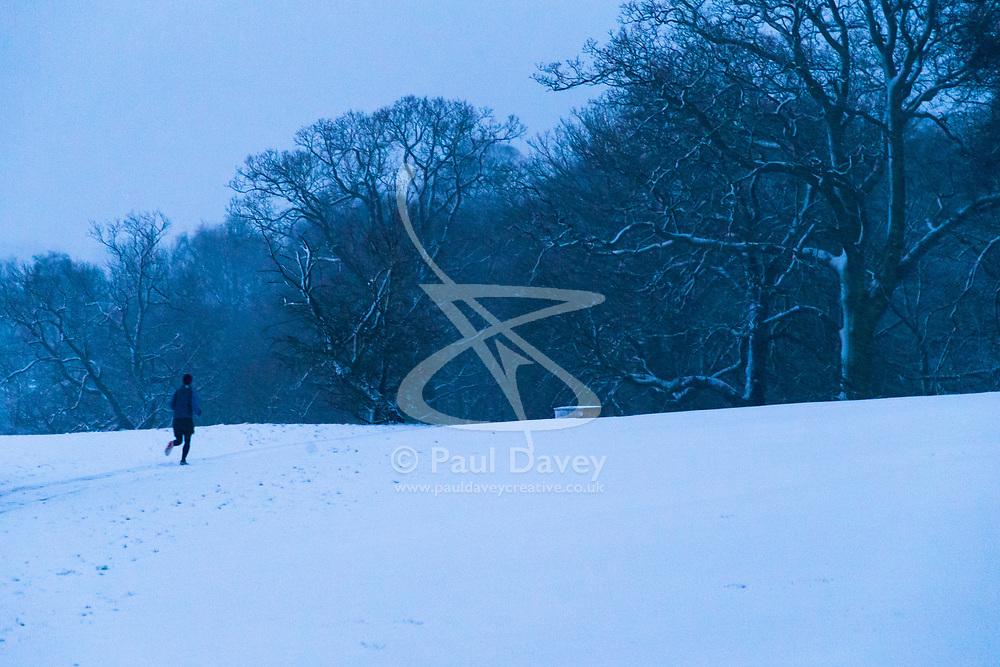 A runner makes his way through the snow on Hampstead Heath. Hampstead, London, February 01 2019.