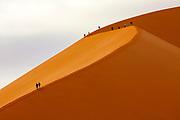 """Column of people climbing """"Big Daddy"""" sand dune, Sossusvlei desert, Namib-Naukluft National Park, Namibia."""