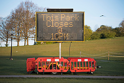 © Licensed to London News Pictures. 18/04/2021. London, UK. A sign warning of a 10pm closure at Primrose Hill in North London. A curfew has been put in to place at the park over the weekend to prevent large gatherings in the evening. Photo credit: Ben Cawthra/LNP