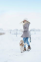 Teenage girl running with her dog in snow covered landscape, Bavaria, Germany