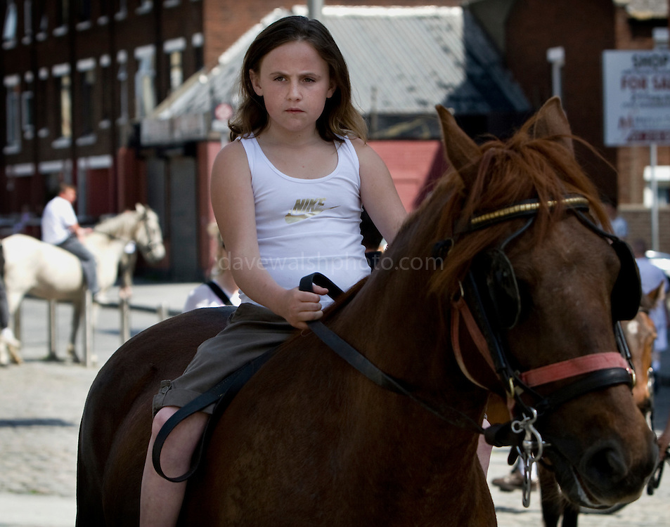 Very serious young girl on horseback at the horse market, Smithfield. ....The horse market at Smithfield, Dublin takes place on the first Sunday of every month. People come from all over Ireland to trade horses and equipment. It's absolute chaos, with young kids galloping across the cobbles on distressed looking ponies, horses whinnying, gardai chasing jaunting cars on their bicycles. A big part of the horse scene involves the keeping of animals, by Dublin urban youth, in gardens or public areas. The Dublin Society for Prevention of Cruelty to Animals says that the market facilitates the sale of horses to under-16s, who are then unable - or unwilling to look after them. Amongst the dozens of horses visible, I did see a couple of examples of cruelty - the most obvious one of all was by an elderly man, kicking his pony in the stomach for no apparent reason. ....There's talks by Dublin City Council of moving the market out of the city - as Smithfield becomes increasingly gentrified, the more urbane of the urban dwellers in the surrounding apartments are apparently unimpresssed with the smell of horse shit once a month!....Editorial Use only.