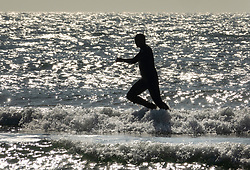 © Licensed to London News Pictures. 10/10/2018. West Wittering, UK. A surfer steps off his board as he tries to catch a wave at West Wittering during a day of unseasonably high temperatures. Photo credit: Peter Macdiarmid/LNP