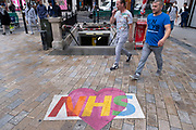 Colourful NHS love heart logo in support of NHS staff and key workers painted onto the street at Oxford Circus under coronavirus lockdown on 1st July 2020 in London, England, United Kingdom. As the July deadline approaces and government will relax its lockdown rules further, the central London remains very quiet, while some non-essential shops are allowed to open with individual shops setting up social distancing systems.