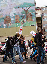 Tottenham, London, August 4th 2015. Family, friends and supporters of alleged gangster Mark Duggan, who was shot and killed by police on 4th August 2011 in Tottenham, commemorate his death which led to widespread uprisings and riots, by marching from Broadwater Farm estate to Tottenham police station. His family is demanding a public inquiry into the role of Operation Trident, set up to fight gun and knife crime amongst the black community, whose officers they accuse of putting guns out on the streets of London. PICTURED: Protesters march through the Broadwater Farm Estate on their way to Tottenham Police Station.  // Contact: paul@pauldaveycreative.co.uk Mobile 07966 016 296