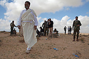 Mcc0030300 . Daily Telegraph..Rebel fighters on the road to Brega accompanied by a white robed man form Tobruk. Brega is now back in the control of Gaddafi's army and there had been an exchange of artillery fire at long range today...Ajdabiyah 31 March 2011