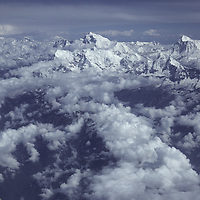 NEPAL, Himalaya, Aerial view of Mts. Everest (center) & Makalu (R) amidst building monsoon clouds.