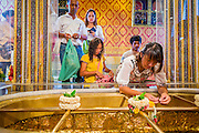 """22 JULY 2013 - PHRA PHUTTHABAT, THAILAND:  People pray at the footprint of Buddha in the Mondop (chapel that houses the footprint) before the Tak Bat Dok Mai at Wat Phra Phutthabat in Saraburi province of Thailand, Monday, July 22. Wat Phra Phutthabat is famous for the way it marks the beginning of Vassa, the three-month annual retreat observed by Theravada monks and nuns. The temple is highly revered in Thailand because it houses a footstep of the Buddha. On the first day of Vassa (or Buddhist Lent) people come to the temple to """"make merit"""" and present the monks there with dancing lady ginger flowers, which only bloom in the weeks leading up Vassa. They also present monks with candles and wash their feet. During Vassa, monks and nuns remain inside monasteries and temple grounds, devoting their time to intensive meditation and study. Laypeople support the monastic sangha by bringing food, candles and other offerings to temples. Laypeople also often observe Vassa by giving up something, such as smoking or eating meat. For this reason, westerners sometimes call Vassa the """"Buddhist Lent.""""    PHOTO BY JACK KURTZ"""
