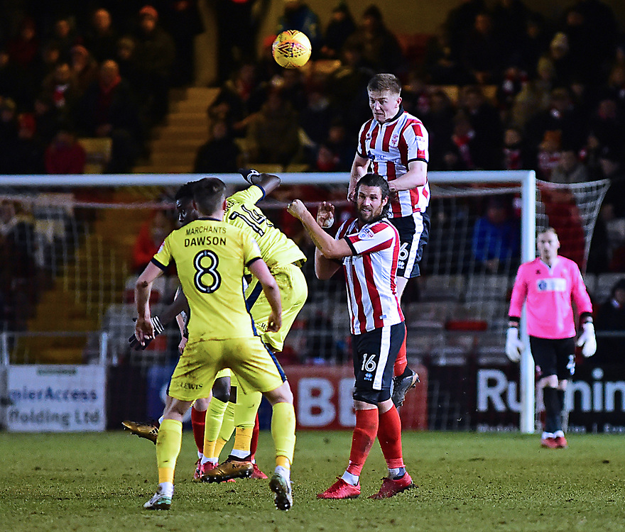 Lincoln City's Scott Wharton gets above Lincoln City's Michael Bostwick and Cheltenham Town's Elijah Adebayo and Kevin Dawson to head clear<br /> <br /> Photographer Andrew Vaughan/CameraSport<br /> <br /> The EFL Sky Bet League Two - Cambridge United v Lincoln City - Friday 9th February 2018 - Abbey Stadium - Cambridge<br /> <br /> World Copyright © 2018 CameraSport. All rights reserved. 43 Linden Ave. Countesthorpe. Leicester. England. LE8 5PG - Tel: +44 (0) 116 277 4147 - admin@camerasport.com - www.camerasport.com