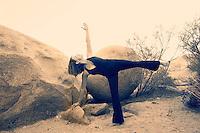 Woman in the yoga pose Ardha Chandrasana or Half Moon asana in a beautiful desert setting.