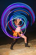 Psychedelic Hula Hoop juggler on the beach at night