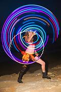 Psychedelic Hula Hoop juggler on the beach at night