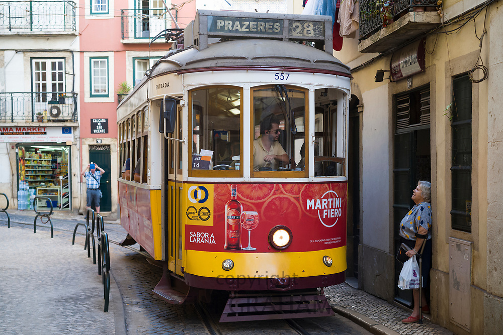 Historic No. 28 Tram carrying local people and tourists -driver chatting with local woman in Alfama District of Lisbon, Portugal