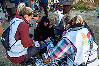 MYTILINI, GREECE - FEBRUARY 09: A group of doctors from The Netherlands comfort a woman after she arrived to a beach in Lesvos after crossing the Aegean sea by dinghy on February 09, 2015 in Mytilini, Greece. Hundreds of refugees arrive everyday at the beaches of Lesvos after being smuggled from the Turkish coast where they board unsafe boats to cross the Aegean sea. Photo: © Omar Havana. All Rights Are Reserved