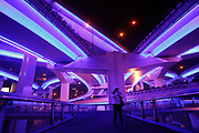 Pedestrians walk near a lit up elevated highway network in Shanghai, China on 04 February 2010. To put on its best face for the upcoming World Expo, the city has been on a massive beautification binge, including lighting, repaving sidewalks and roads, and even painting the exterior of resident's houses.