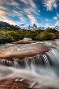 FitzRoy waterfall under famous rock peak Cerro FitzRoy ( El Chalten) , high wind cloud at dusk, Parque Nacional Los Glaciares, Patagonia, Argentina