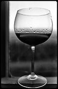 Glass of wine on window sill.