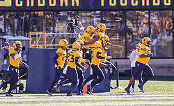 Oct 31, 2020; Morgantown, West Virginia, USA; West Virginia Mountaineers linebacker Dylan Tonkery (10) celebrates with teammates after scoring a touchdown off can interception during the third quarter against the Kansas State Wildcats at Mountaineer Field at Milan Puskar Stadium. Mandatory Credit: Ben Queen-USA TODAY Sports