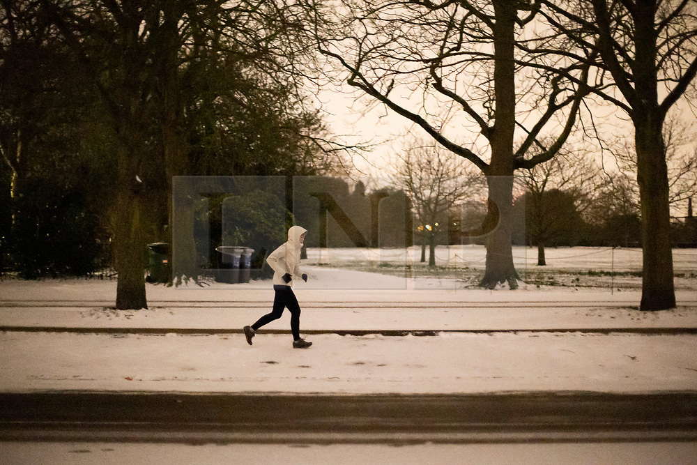 © Licensed to London News Pictures. 09/02/2021. London, UK. A member of the public exercises in a snowy Greenwich Park in South East London. Snow is expected for large parts of the UK and yellow and amber weather warnings in place in parts of England as Storm Darcy hits the UK. Photo credit: George Cracknell Wright/LNP