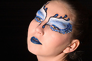 young teenage female model with blue and white elaborate make up mask on black background model released studio shot
