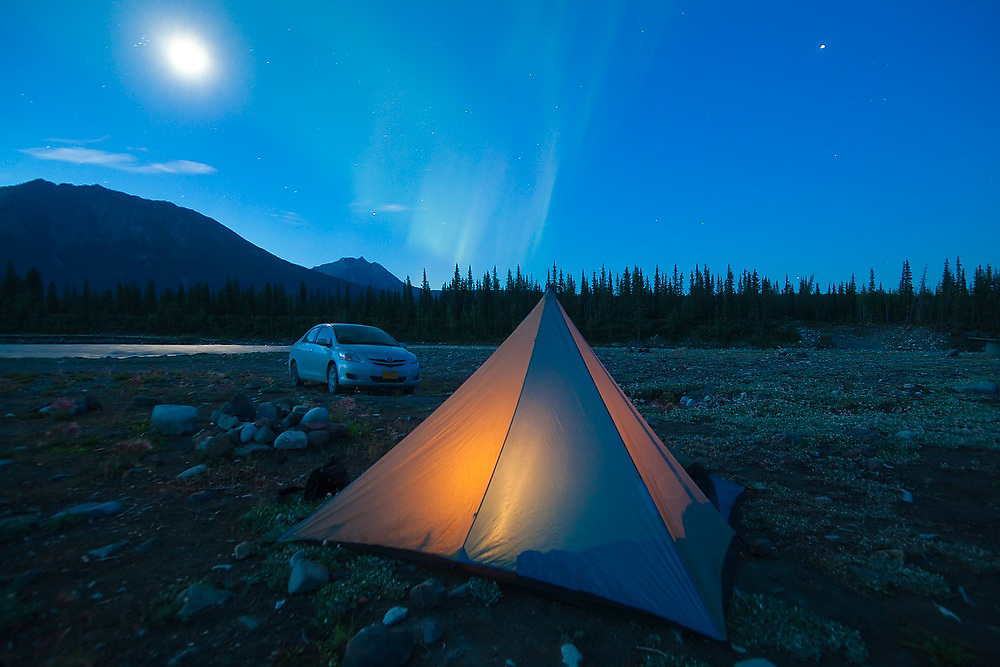 A glowing tent, a parked car, the moon and the Northern Lights on the shore of the Kennicott River at a campground near McCarthy, Alaska.